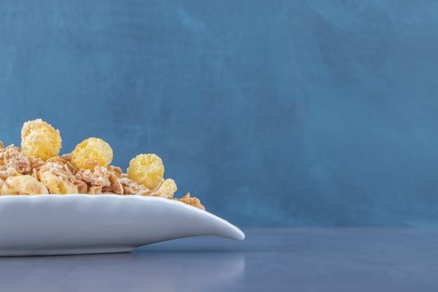 Honingmaïsring met muesli in een bord, op de marmeren tafel.