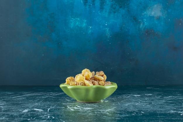 Honingmaïsring met muesli in een kom, op de blauwe tafel.