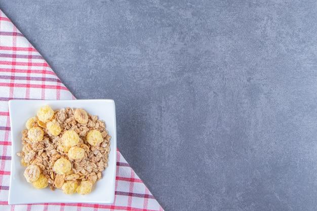 Honingmaïsring met muesli in een kom op een theedoek, op de marmeren tafel.
