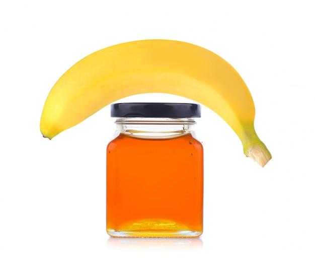 Honingpot en banaan op wit