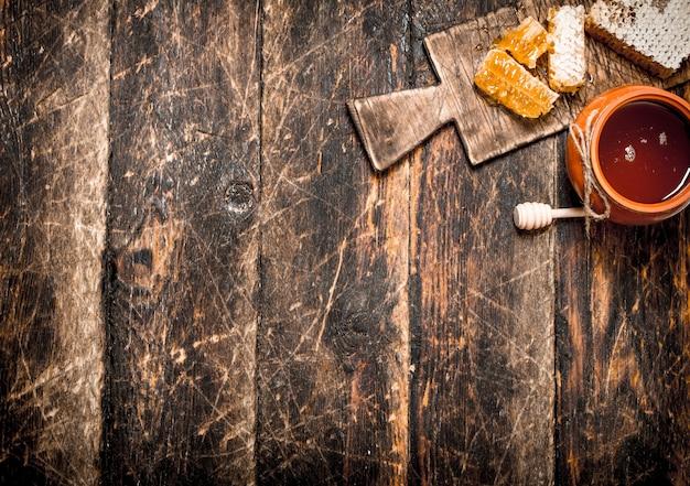 Honingpot en honingraat met een houten lepel op houten tafel.