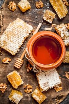 Honingpot en honingraat met noten op rustieke tafel.