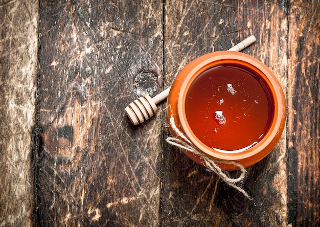 Honingpot met een houten lepel op houten tafel.