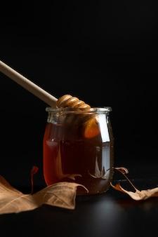 Honingpot met lepel met herfstbladeren