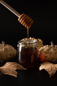 Honingpot met lepel met pompoenen en herfstbladeren