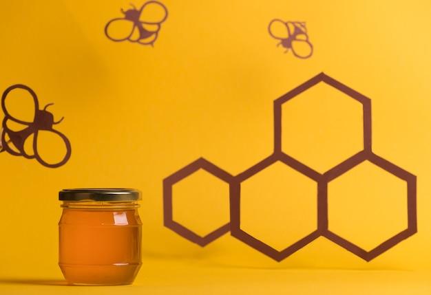 Honingpot onder papierkunst met papiersnijder bijen en honingraten gezond snoep biologisch voedselconcept