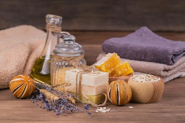 Honingraat, cosmetische olie, zeezout, haver en handgemaakte zeep met honing op rustieke houten achtergrond. natuurlijke ingrediënten voor zelfgemaakte gezichts- en lichaamsmasker of scrub. gezonde huidverzorging. spa-concept.