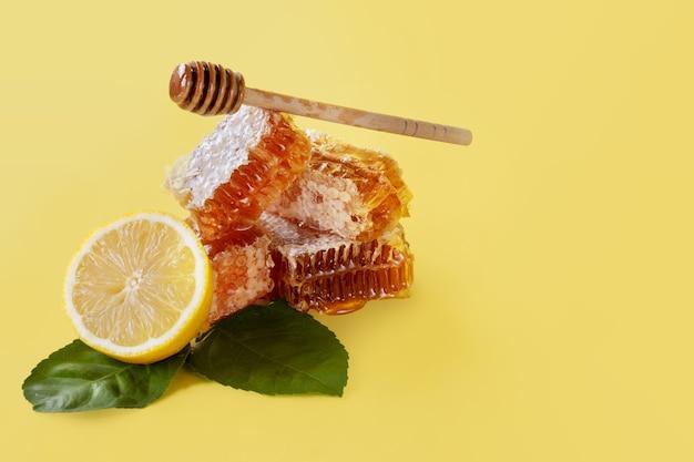 Honingraat en citroen met houten stok op gele achtergrond