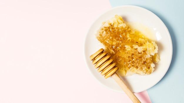 Honingraat en houten honingsdipper in plaat op dubbele achtergrond