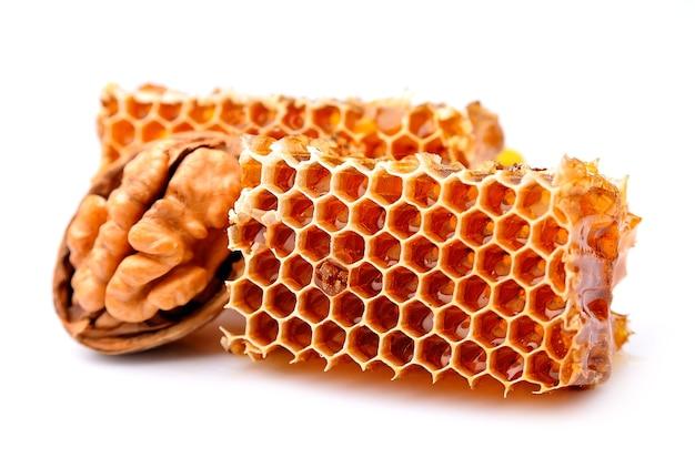 Honingraat en walnoten close-up op wit.