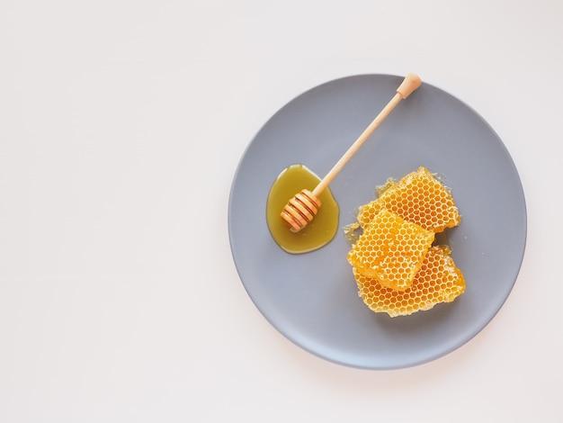 Honingraat met beer op een blauw bord plat lag natuurlijke bio honing