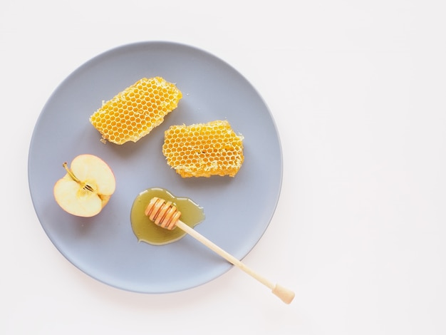 Honingraat met dipper en appelschijf op een plaat natuurlijke producten