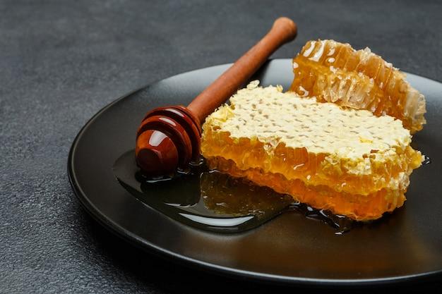 Honingraat met honing op plaat op donkere betonnen tafel
