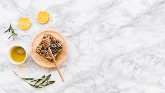 Honingraat met olijfolie op witte marmeren achtergrond
