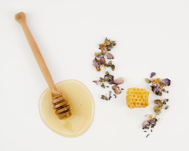 Honingraat tussen gedroogde bloemen met houten lepel
