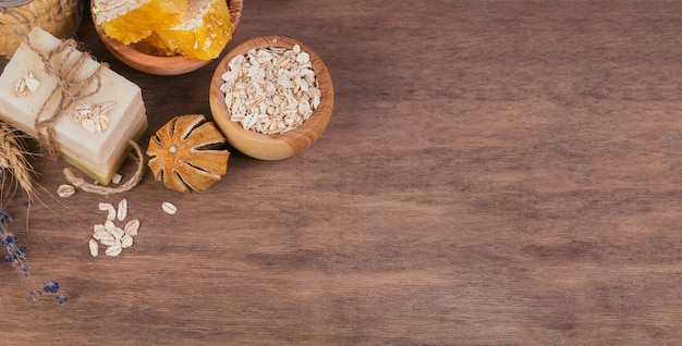 Honingraat, zeezout, havermout en handgemaakte zeep met honing op rustieke houten achtergrond. natuurlijke ingrediënten voor zelfgemaakte gezichts- en lichaamsmasker of scrub. gezonde huidverzorging. spa-concept. bovenaanzicht