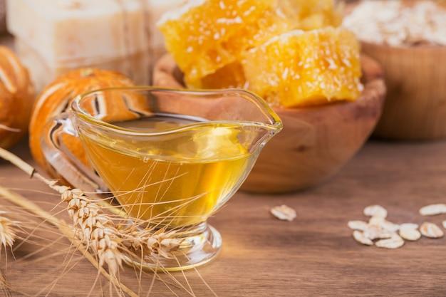 Honingraat, zeezout, havermout en handgemaakte zeep met honing op rustieke houten achtergrond. natuurlijke ingrediënten voor zelfgemaakte gezichts- en lichaamsmasker of scrub. gezonde huidverzorging. spa-concept. detailopname