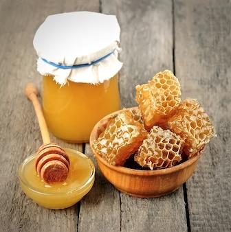 Honingraathoning en vloeibare honing op het bord