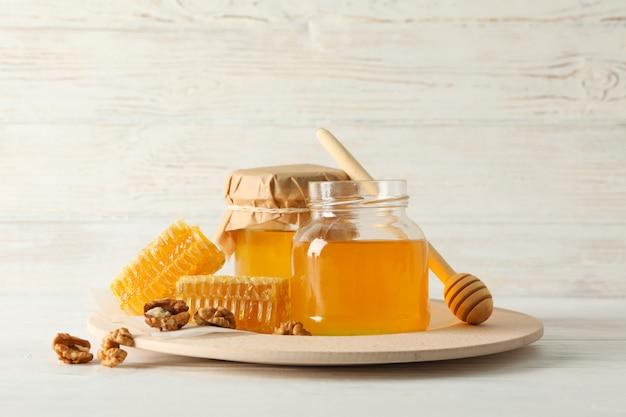 Honingraten, walnoten, beer en potten met honing op houten achtergrond