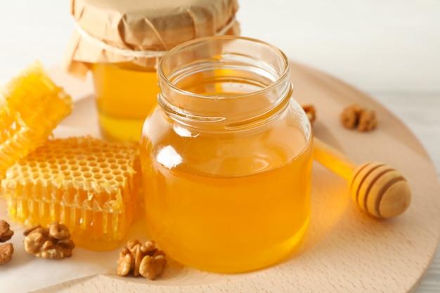 Honingraten, walnoten, beer en potten met honing op houten
