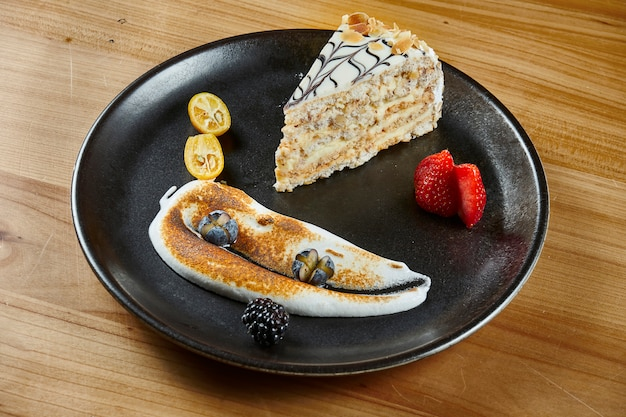 Honingscake met lagen en gebakjeroom op houten oppervlakte. segment van heerlijke medovik cake. detailopname. lekker bakkerijconcept. selectieve aandacht