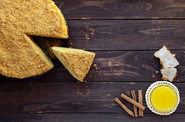 Honingscake op een donker hout. een stuk snijden.