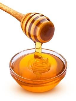 Honingsdipper en gietende die honing op wit wordt geïsoleerd