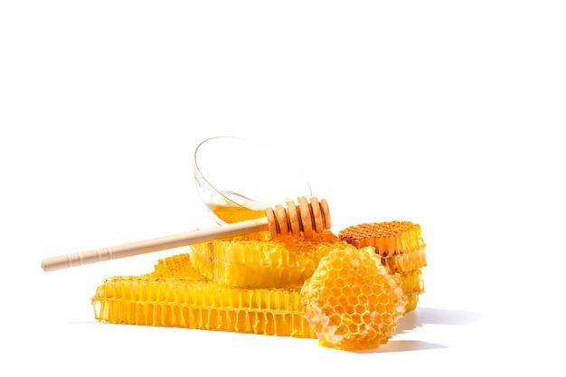 Honingsdipper en kom met honing die op witte oppervlakte wordt geïsoleerd. natuurlijke bijenhoning.