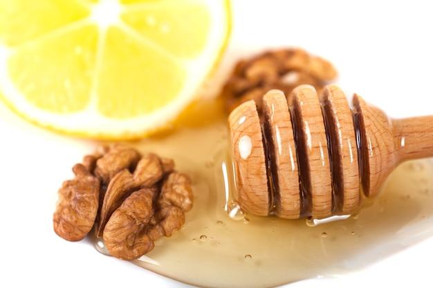 Honingsdipper, walnoot en citroen op een witte achtergrond.