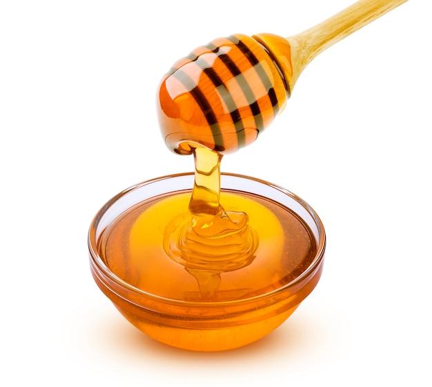 Honingsstok en gietende die honing op wit wordt geïsoleerd