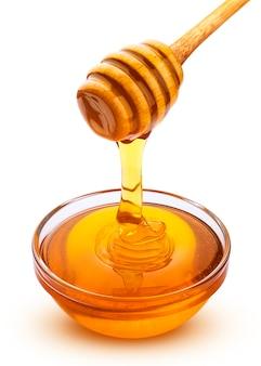 Honingsstok en kom gietende die honing op witte achtergrond met het knippen van weg wordt geïsoleerd