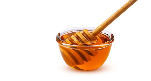 Honingsstok en kom honing op wit met het knippen van weg wordt geïsoleerd die