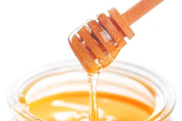 Honingsstok met stromende die honing op wit wordt geïsoleerd