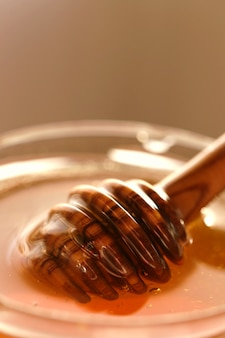 Honingstokje. honingpot met lepel. honingstokje in een pot met honing