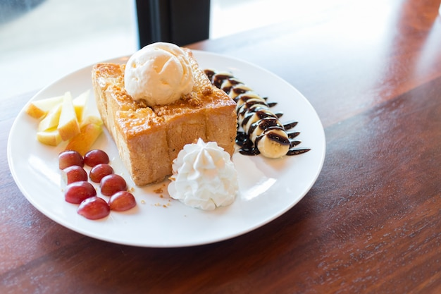 Honingtoost met vanille-ijs, slagroom en chocoladesiroop. geserveerd met banaan, druif en appel