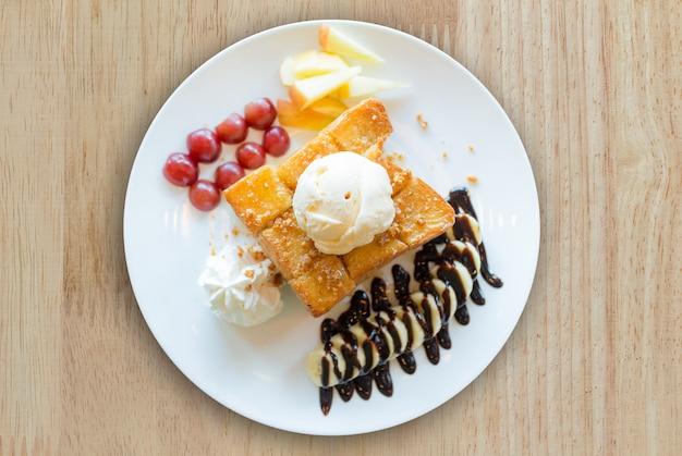 Honingtoost met vanille-ijs, slagroom en chocoladesiroop.