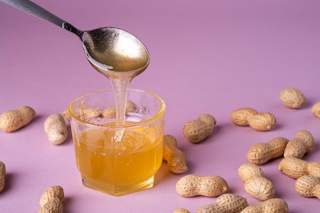 Honingvloeistof in glas met metalen lepel met pinda's op paarse muur