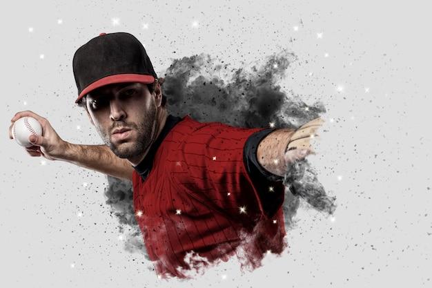Honkbalspeler met een rood uniform dat uit een rookstoot komt.