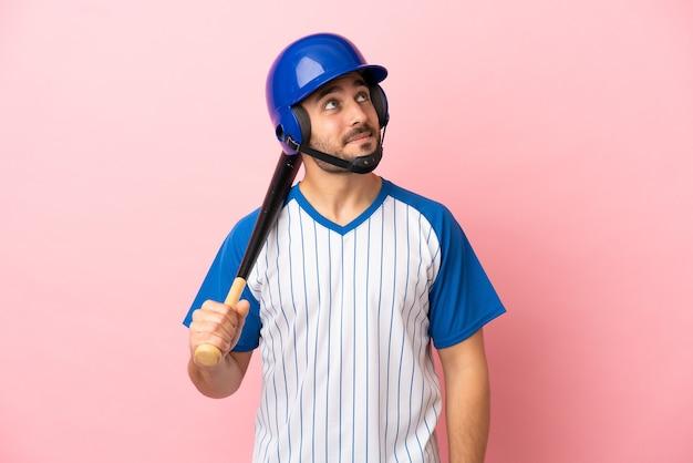 Honkbalspeler met helm en vleermuis geïsoleerd op roze achtergrond die een idee denkt terwijl hij omhoog kijkt