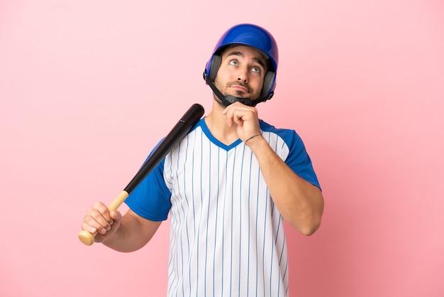 Honkbalspeler met helm en vleermuis geïsoleerd op roze achtergrond en opzoeken