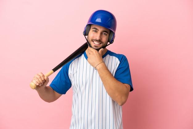 Honkbalspeler met helm en vleermuis geïsoleerd op roze achtergrond gelukkig en lachend