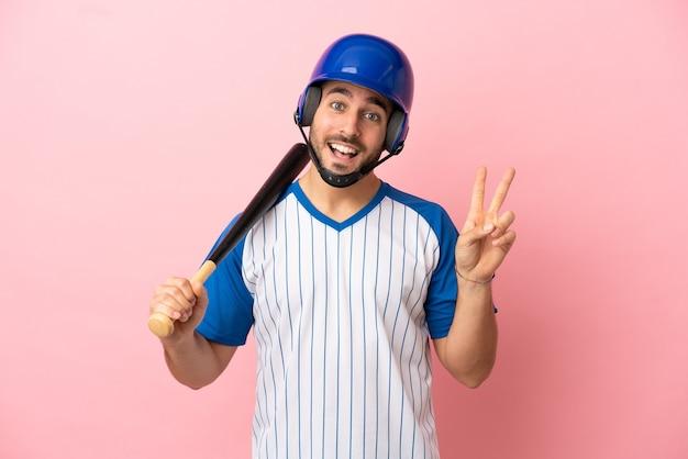 Honkbalspeler met helm en vleermuis geïsoleerd op roze achtergrond glimlachend en overwinningsteken tonen