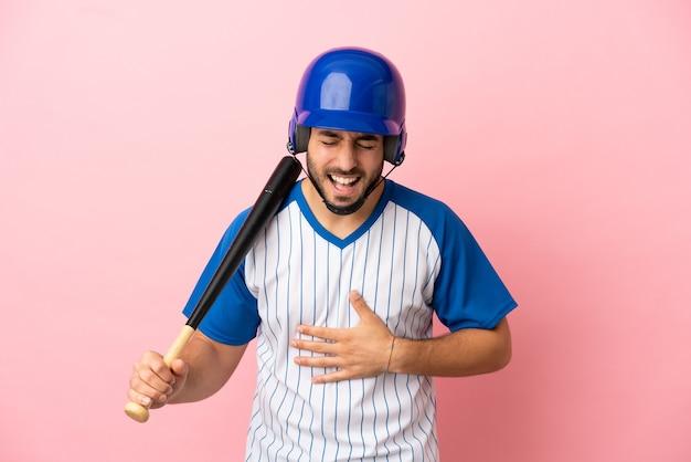 Honkbalspeler met helm en vleermuis geïsoleerd op roze achtergrond glimlachend veel