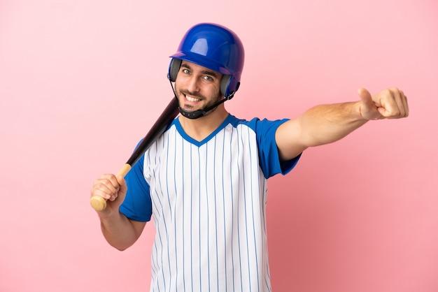 Honkbalspeler met helm en vleermuis geïsoleerd op roze achtergrond met een duim omhoog gebaar