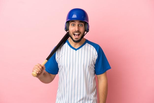 Honkbalspeler met helm en vleermuis geïsoleerd op roze achtergrond met verrassing gezichtsuitdrukking