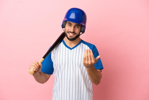 Honkbalspeler met helm en vleermuis geïsoleerd op roze achtergrond uitnodigend om met de hand te komen. blij dat je gekomen bent