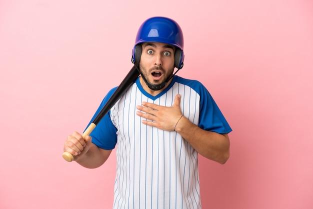 Honkbalspeler met helm en vleermuis geïsoleerd op roze achtergrond verrast en geschokt terwijl hij naar rechts kijkt