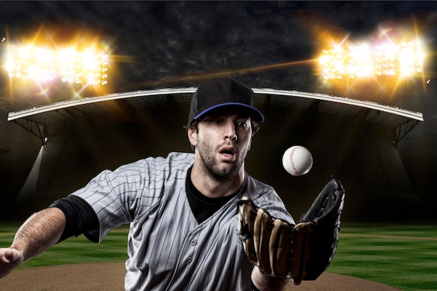 Honkbalspeler op een blauw uniform op honkbalstadion.