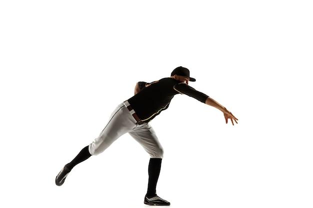 Honkbalspeler, werper in een zwart uniform oefenen en trainen geïsoleerd op een witte muur. jonge professionele sportman in actie en beweging. gezonde levensstijl, sport, bewegingsconcept.