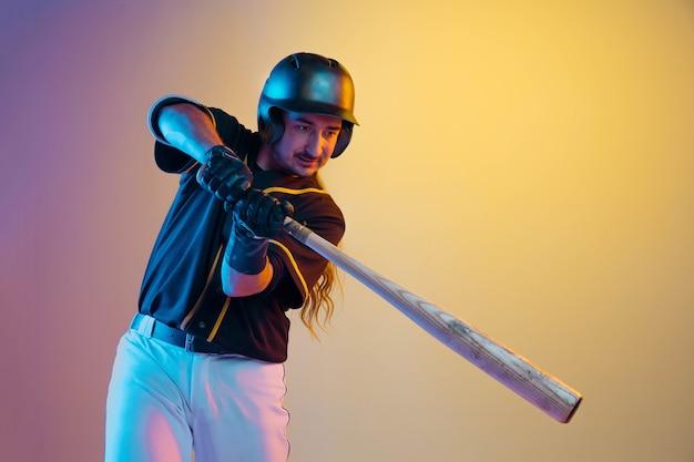 Honkbalspeler, werper in een zwart uniform poseren zelfverzekerd op de achtergrond met kleurovergang in neonlicht.